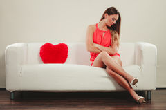 Sad woman with heart shape pillow. Valentines day. Sad unhappy young woman girl with red heart shape pillow sitting on white sofa couch. Valentines day love Royalty Free Stock Images