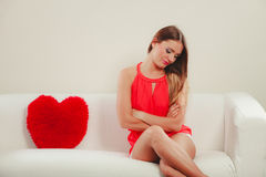 Sad woman with heart shape pillow. Valentines day. Stock Photography