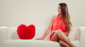 Sad woman with heart shape pillow. Valentines day. Stock Images