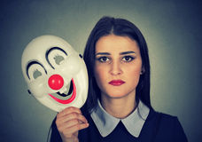Sad woman holding clown mask expressing cheerfulness happiness Stock Photo