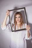 Sad woman holding a frame in his hands. Sad beautiful girl holding a frame in his hands Stock Image