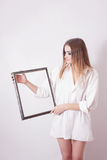 Sad woman holding a frame in his hands. Sad beautiful girl holding a frame in his hands Royalty Free Stock Photo