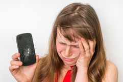 Sad woman is holding mobile phone with broken screen. Sad woman is holding mobile phone in her hand with broken screen royalty free stock photos