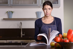 Sad Woman Holding Recipe Book at the Kitchen. Sad Young Woman Wearing Apron Holding Recipe Book at the Kitchen While Looking at the Camera Stock Photos