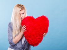 Sad woman holding red pillow in heart shape Stock Photos