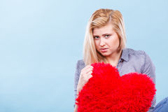 Sad woman holding red pillow in heart shape Stock Image