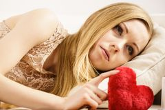 Sad woman holding red pillow in heart shape. Sad or serious woman feeling lonely and unloved holding little red pillow in heart shape royalty free stock image