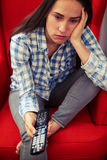 Sad woman holding remote control and watching Stock Photos