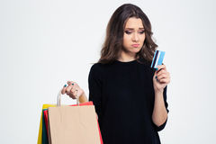 Sad woman holding shopping bags and bank Stock Photo