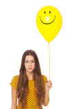Sad woman holding smiley face balloon Stock Photography