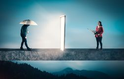 Sad woman holds an umbrella and goes to a door portal, coming ou Stock Image