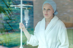 Sad woman at the hospital. Young sad woman standing with drip at the hospital stock photos