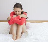 Sad woman hugging knees on bed at home Royalty Free Stock Photography