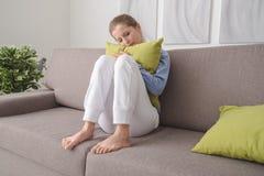 Sad woman hugging a pillow Stock Image