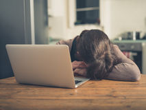 Sad woman with laptop in kitchen Royalty Free Stock Images