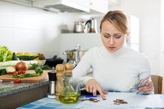 Sad woman with last money and bills. Portrait of upset housewife counting last money in kitchen Royalty Free Stock Photography