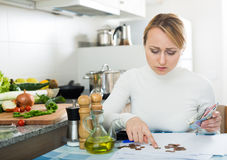 Sad woman with last money and bills. Portrait of upset housewife counting last money in kitchen Stock Photo