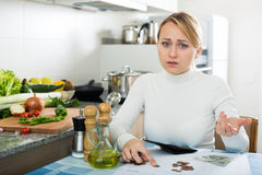Sad woman with last money and bills. Portrait of upset housewife counting last money in kitchen Royalty Free Stock Images