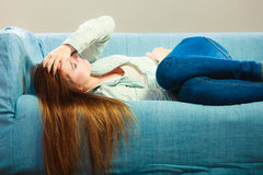 Sad woman laying on couch Stock Images