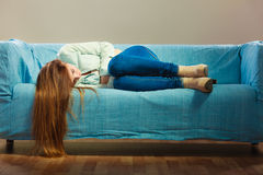 Sad woman laying on couch Royalty Free Stock Photos