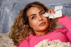 Sad woman lays in bed alone and cries at home. Sad beautiful woman lays in bed alone and cries at home royalty free stock images