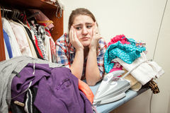 Sad woman leaning against huge pile of not ironed clothes Royalty Free Stock Photo