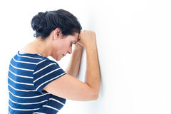 Sad woman leaning against the wall Stock Photos