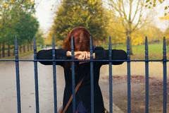 Sad woman leaning on gate in park Royalty Free Stock Images
