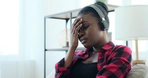 Sad woman listening music on headphones