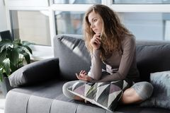 Sad woman locating on comfortable couch. Full length side view sorrowful female sitting on cozy sofa in living room. Melancholy concept Stock Image