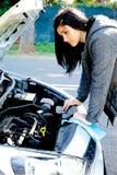 Sad woman looking broken engine of car Royalty Free Stock Photos