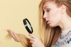 Sad woman looking at damaged hair ends. Stock Photography
