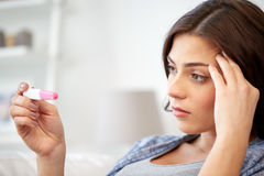 Sad woman looking at home pregnancy test Stock Photo