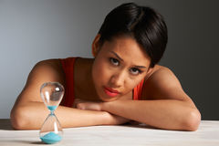 Sad Woman Looking At Hourglass Royalty Free Stock Photo
