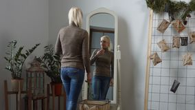 Sad woman looking in the mirror at her wrinkles stock video footage