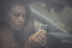 Sad woman looking in the mobile phone and reading message in the window with rain drop in the car. Face of young female behind rain car window. Loneliness and Royalty Free Stock Photography