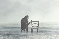 Sad woman looking nostalgically at her lover`s empty chair Stock Photo