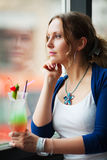Sad beautiful woman looking out window    Stock Photo