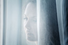 Sad woman looking out the window Stock Images