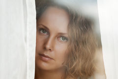 Sad woman looking out the window Stock Image