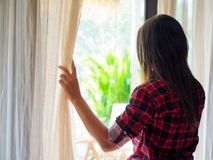 Sad Woman looking out a window, indoors. Rear view of a young woman holding the curtains open to look out of a large light window at home, interior. Positive Royalty Free Stock Image