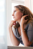 Sad woman looking through the window Royalty Free Stock Photography