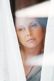 Sad woman looking through the window Stock Photography