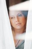 Sad woman looking through the window. Sad beautiful woman looking through a window Stock Photography