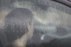 Sad woman looking through the window with rain drop in the car. Face of young female behind rain car window. Loneliness and depression concept. Psychology Stock Images