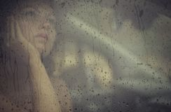 Sad woman looking through the window with rain drop in the car. Face of young female behind rain car window. Loneliness and depression concept. Psychology Royalty Free Stock Photo