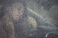 Sad woman looking through the window with rain drop in the car. Face of young female behind rain car window. Loneliness and depression concept. Psychology Stock Image