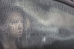 Sad woman looking through the window with rain drop in the car. Face of young female behind rain car window. Loneliness and depression concept. Psychology Royalty Free Stock Images