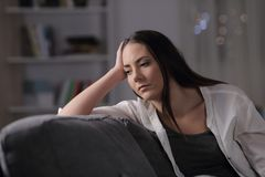 Sad woman looks away in the night at home royalty free stock images