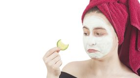 Sad woman loonikg at cucumber for beauty mask Royalty Free Stock Photos